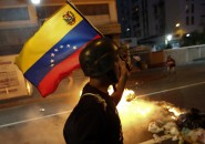 An opposition demonstrator carries a Venezuelan flag as he walks past a burning barricade during a protest in Caracas
