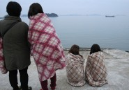 Relatives of passengers of a sunken ship wrapped in blankets look tow