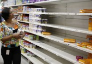 A woman picks up groceries at a supermarket in Caracas