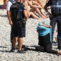 Police controlling on the beach and first person to be fined wearing a burkini on the promenade des anglais beach in Nice on 23/08/2016