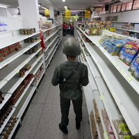 "(FILE) A soldier stands guard inside a supermarket in San Antonio de Tachira, Venezuela, close to the border with Colombia, on August 27, 2015. Venezuela's President Nicolas Maduro decreed a state of ""economic emergency"" on January 15, 2016, seizing the initiative in a political standoff with the opposition in the oil-rich state. ""A state of economic emergency is declared across the whole territory of the nation"" in accordance with the constitution, ""for 60 days,"" read the decree published by the official state journal.   AFP PHOTO / GEORGE CASTELLANOS / AFP / George CASTELLANOS"