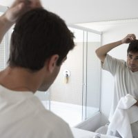 Man styling hair in bathroom mirror, rear view (focus on reflection)