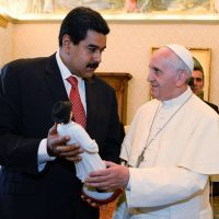 Pope Francis (R) and Venezuelan President Nicolas Maduro exchange gifts during a private audience in the pontiff's library on June 17, 2013 at the Vatican. AFP PHOTO / POOL / ANDREAS SOLARO