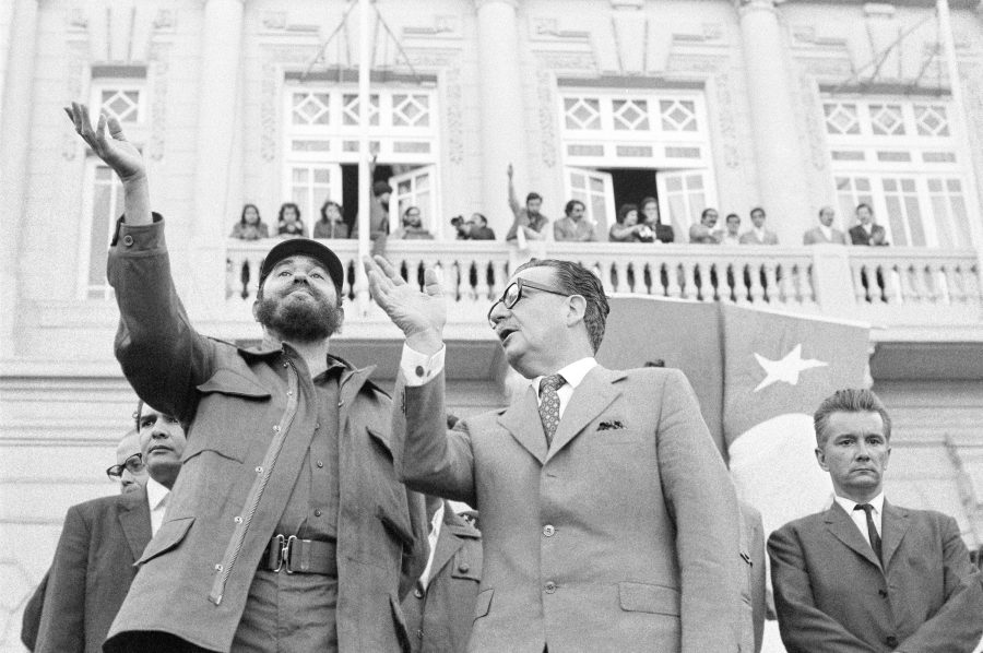 Chile's President Salvador Allende, right, talks to Cuba's Fidel Castro, as they acknowledge cheers during the outdoor rally they attended at this Pacific Ocean port in Valparaiso, Chile  Nov. 30, 1971. (AP Photo)