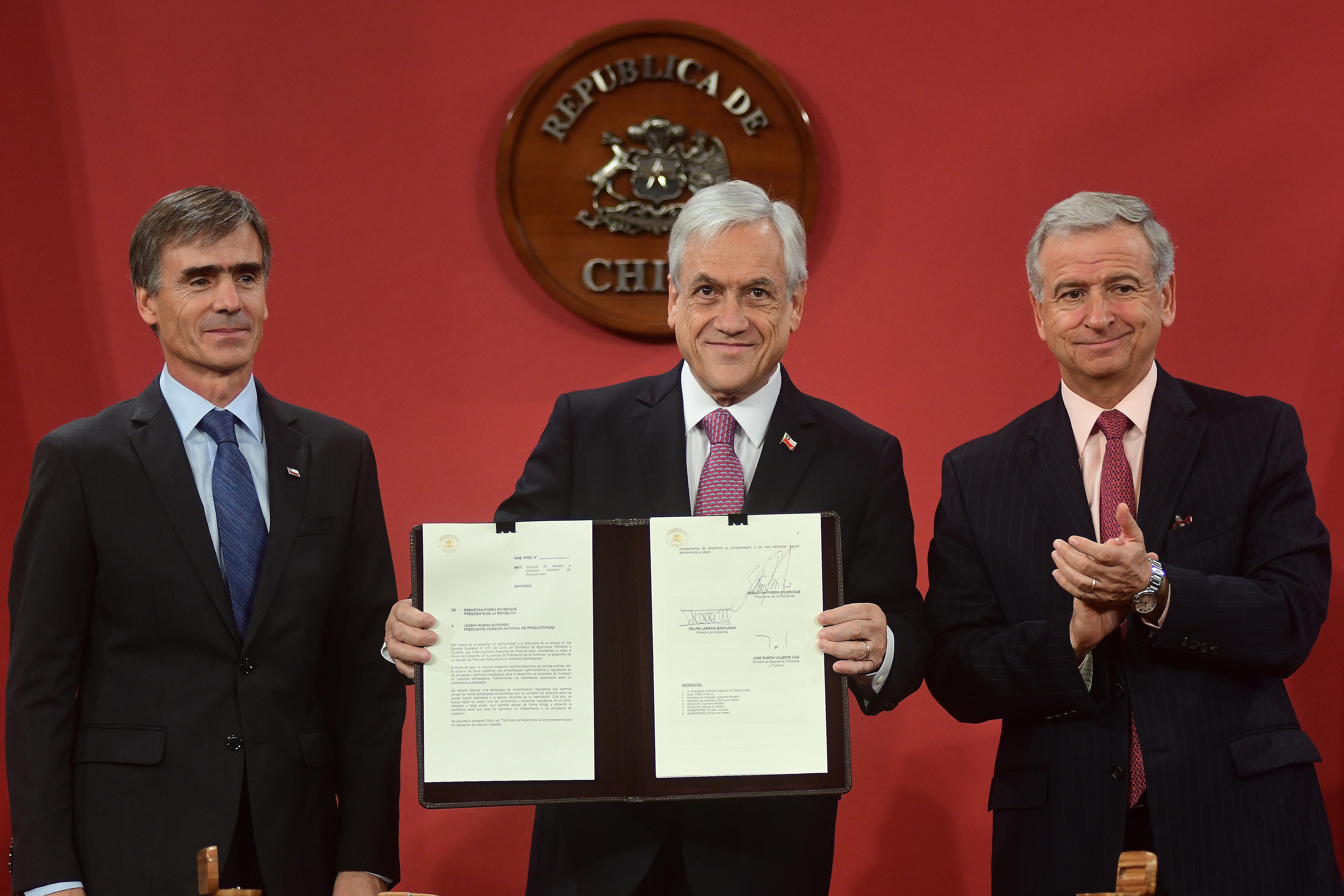 El Presidente de la República, Sebastián Piñera, junto al Ministro de Economía, Fomento y Turismo, José Ramón Valente, firman el proyecto de ley de agenda proinversión y el decreto que establece la Oficina de Gestión de Proyectos Sustentables.