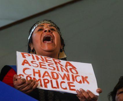 """15 de Noviembre de 2018 / SANTIAGO Una mapuche se manifiesta con un cartel con la leyenda """"Piñera Asesino Chadwick Complice"""", al interior de la casa central de la Universidad de Chile, durante una conferencia de prensa de diversas organizaciones sociales, repudiando el asesinato del comunero Camilo Catrillanca. FOTO: HANS SCOTT / AGENCIAUNO"""